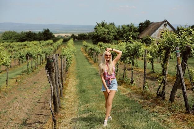 田舎でポーズをとって夏の服装の若い女性