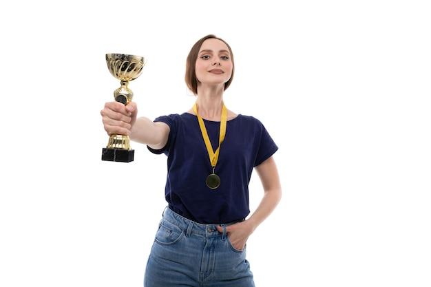 티셔츠와 청바지를 입은 젊은 여성이 골드 컵을 보유하고 있습니다.
