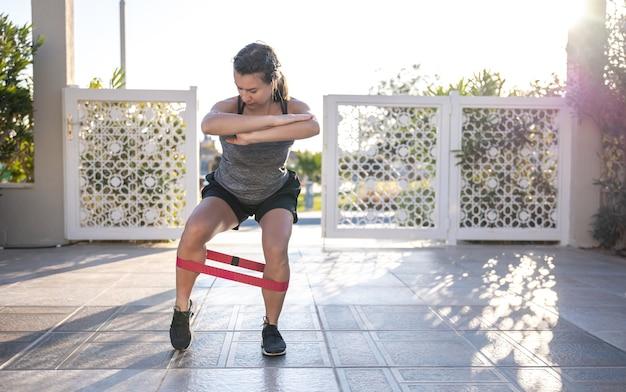 タンクトップとショートパンツを着た若い女性が、屋外でエキスパンダーを持ってスポーツに出かけます。