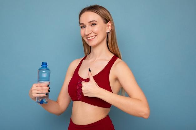 Молодая женщина в спортивном костюме пьет воду на синем фоне