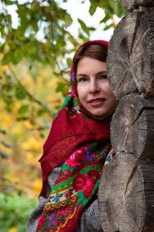 Молодая женщина в традиционном русском платке смотрит из-за угла деревянного дома. павловский платок красный ярославль россия 10.10.2019