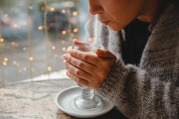Молодая женщина в теплой куртке сидит в кафе за столиком у окна и дует на стакан кофе