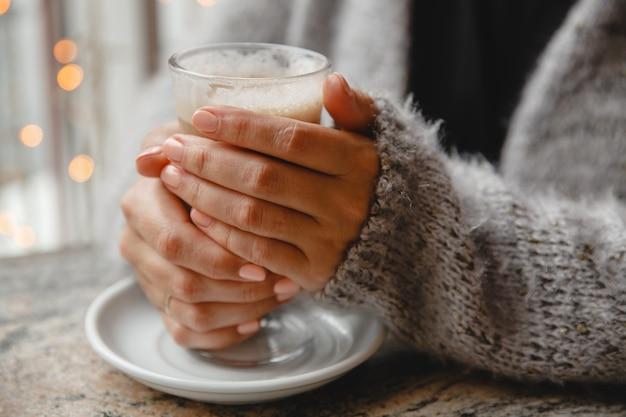 Молодая женщина в теплой куртке сидит в кафе за столиком у окна и греет руки стаканом кофе.