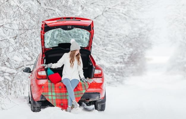 Молодая женщина в теплом свитере, шапке и варежках сидит на клетчатом пледе в багажнике красной машины на фоне зимнего леса.