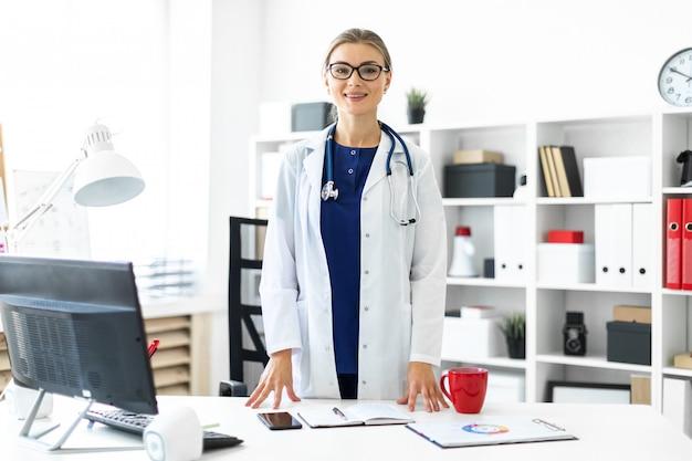 Молодая женщина в белом халате стоит возле стола в своем кабинете. стетоскоп висит вокруг ее шеи.