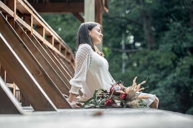 하얀 드레스를 입은 젊은 여성이 이국적인 꽃 꽃다발을 들고 나무 다리에 앉아 있습니다.