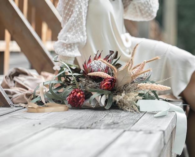 白いドレスを着た若い女性は、エキゾチックなプロテアの花の花束と木製の橋の上に座っています。