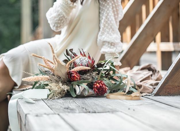 하얀 드레스를 입은 젊은 여성이 이국적인 프로테아 꽃 꽃다발을 들고 나무 다리에 앉아 있습니다.
