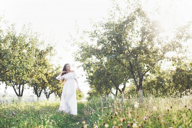 하얀 긴 드레스에 젊은 여자는 정원에서 걷고있다. 나무의 잎을 통해 아름 다운 일몰