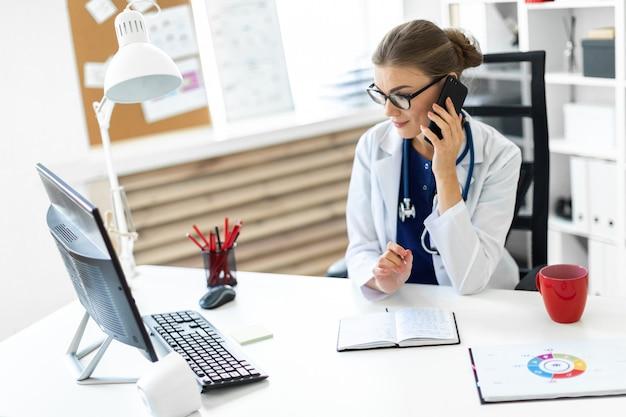 Молодая женщина в белом халате сидит за столом в офисе, разговаривает по телефону и держит ручку в руке. стетоскоп висит вокруг ее шеи.