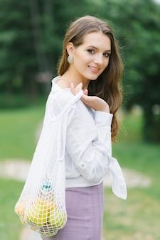 흰색 셔츠를 입은 젊은 여성, 라일락 드레스와 친환경 과일 가방. 제로 웨이스트의 개념.