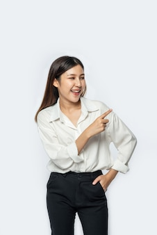 Молодая женщина в белой рубашке и указывая вверх