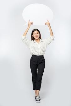 Молодая женщина в белой рубашке держит символ коробки мыслей