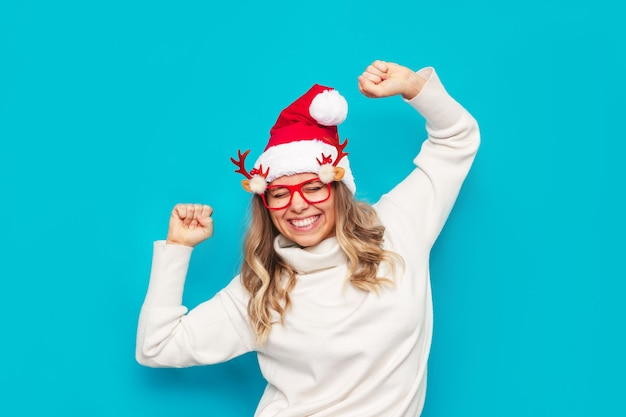 白いセーターのサンタの帽子をかぶった若い女性は、クリスマス新年のコンセプトを手に満足しています