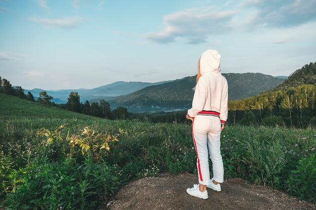 白いトラックスーツを着た若い女性が夕方の美しい山々を遠くから眺めています。山に登る。野外活動。山への旅。