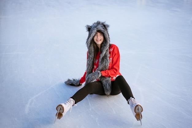 Молодая женщина в волчьей шляпе, одетая в спортивную одежду, сидит на льду и улыбается. концепция отдыха и спорта.