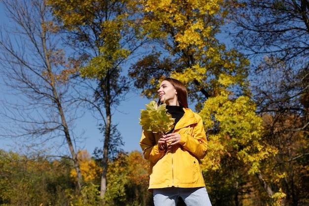 明るい日に秋の背景の前に黄色い紅葉と黄色のレインコートを着た若い女性。秋の気分