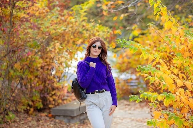 Молодая женщина в осеннем парке в фиолетовом свитере