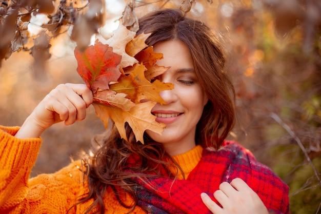 Молодая женщина в осеннем парке в оранжевом свитере