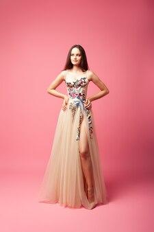 이브닝 드레스를 입은 젊은 여성이 외딴 배경에 서 있고 무성한 공을 든 아름다운 여성 ...