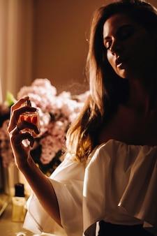 Молодая женщина в вечернем платье с духами стоит перед домашним туалетным столиком. девушка пользуется духами перед тем, как пойти на вечеринку.