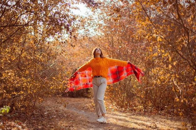 Молодая женщина в оранжевом свитере закутывается в шарф в осеннем парке