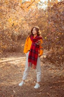 Молодая женщина в оранжевом свитере закутывается в шарф в осеннем парке Premium Фотографии
