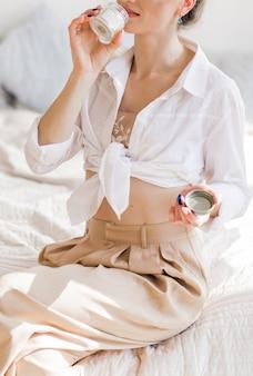 Молодая женщина в бежевых брюках и белой блузке держит в руках свечу и наслаждается ее ароматом. комната залита солнечным светом. фото
