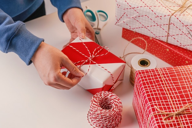 Молодая женщина в синем обертывает, упаковывает рождественский подарок для детей в красивую, красную, белую обертку с мерцающим светом, образ жизни.