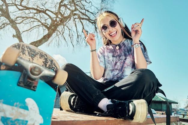 カジュアルな服とサングラスをかけた若い女性が音楽を聴きながら日没時に公園に座っています