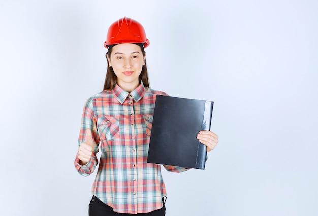 黒いフォルダーを保持し、親指を上に表示しているクラッシュヘルメットの若い女性。
