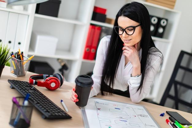 Молодая женщина в очках стоит возле стола и держит в руке стакан кофе