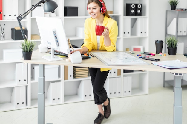 ヘッドフォンの若い女性がコンピューターで働いており、赤いカップから飲んでいます。