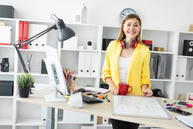 ヘッドフォンの若い女性は、彼女の手に赤いマグカップを持つテーブルの近くに立っています。