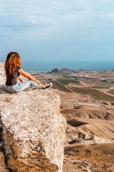 Молодая женщина в джинсах сидит на скале в долине в крыму