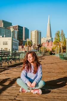 샌프란시스코의 아침에 청바지를 입은 젊은 여성이 부두의 나무 바닥에 앉아 있다