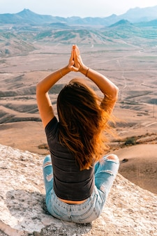 Молодая женщина в позе йоги сидит на скале в долине