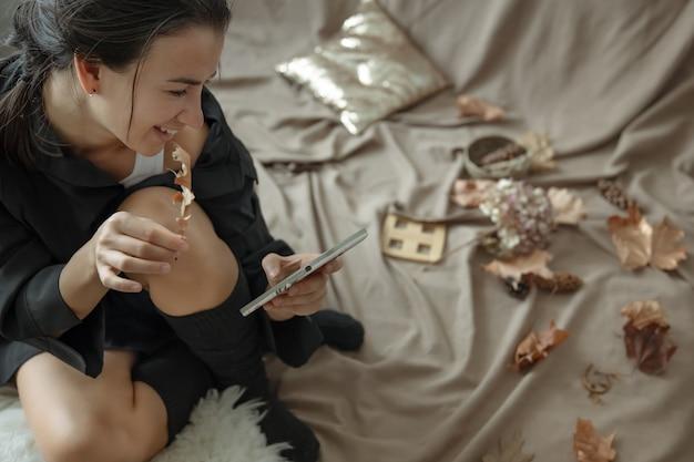 니트 스타킹을 입은 젊은 여성이 가을 낙엽 사이에서 아늑한 침대에서 전화를 사용합니다.