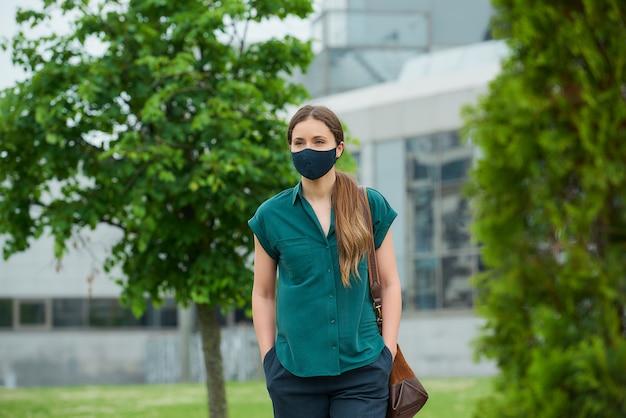 의료 얼굴 마스크에 젊은 여자가 바지 주머니에 손을 밀어 나무 근처 산책