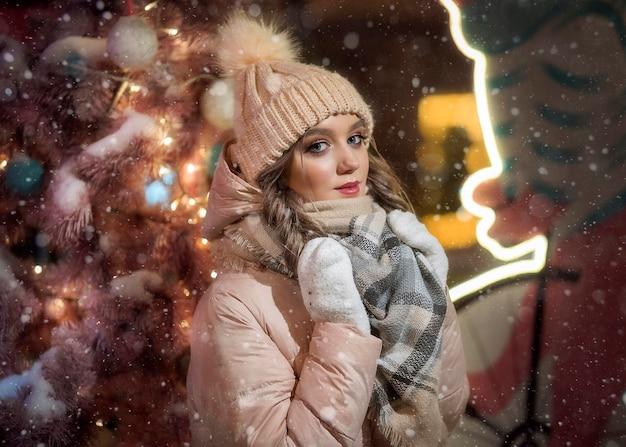 ミトンとピンクのクリスマスツリーの横にある帽子の若い女性。ベージュのジャケットでかわいい女の子の冬の肖像。女性のクリスマスの肖像画。
