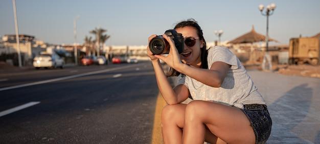 Молодая женщина в шортах и футболке летом сидит на тротуаре с профессиональной камерой