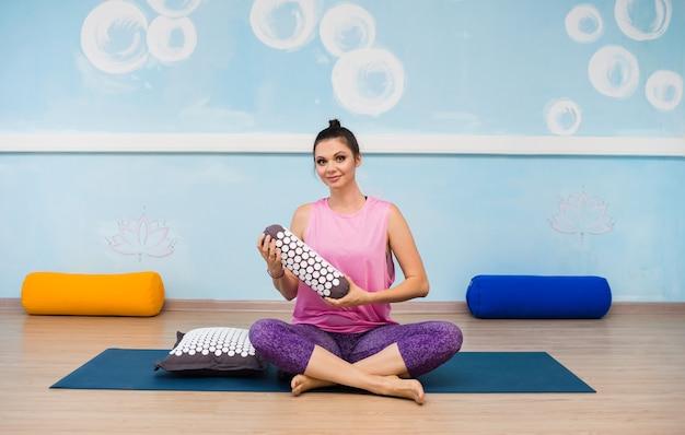 Молодая женщина в спортивной одежде сидит на коврике с ортопедической подушкой