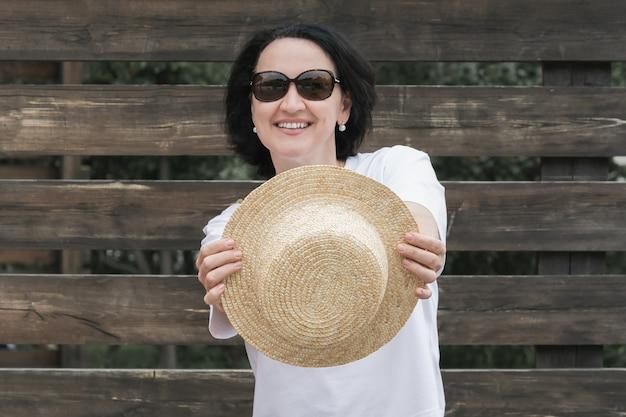 夏服を着た若い女性が暗い柵を背景に立ち、麦わら帽子を手に持って微笑む。
