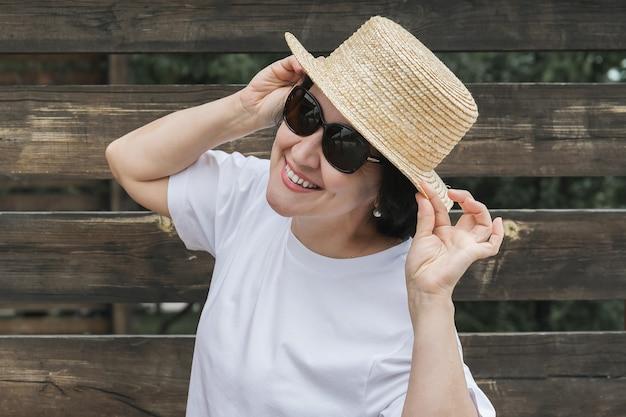 麦わら帽子とサングラスをかけた夏服を着た若い女性が、暗い柵を背景に立って微笑んでいます。