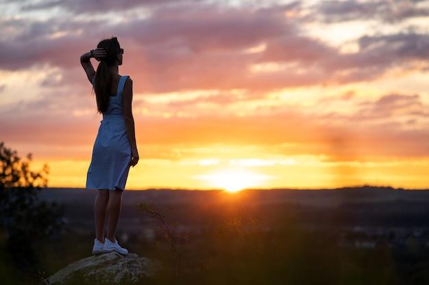 밝은 노란색 일몰의 전망을 즐기고 야외에서 서 있는 여름 드레스에 젊은 여자.