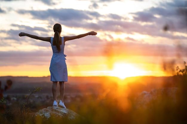 밝은 노란색 일몰을 바라보며 팔을 벌리고 야외에 서 있는 여름 드레스를 입은 젊은 여성.