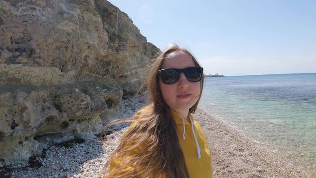 선글라스를 쓴 젊은 여성이 바다에서 자신을 촬영하고 있습니다. 바다에서 휴식을 취하십시오. 여행블로그. 4k uhd