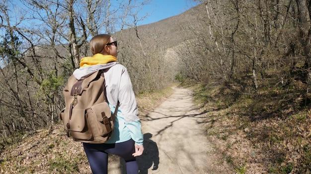 大きなバックパックを背負ったサングラスをかけた若い女性が森の中を歩き、木々を見ます。自然へのハイキング。 4k uhd