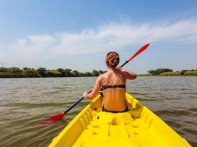 カタルーニャの自然公園、エスターティットのビーチの隣の川でカヌーカヌーをしている若い女性