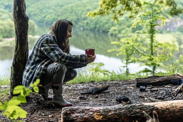 川の近くの森の若い女性が火事で暖まり、温かい飲み物を飲む